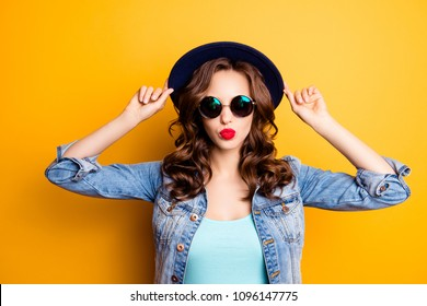 Portrait of cool charming girl holding hat on her head sending kiss with pout lips isolated on yellow background having fashionable look, rest relax leisure concept