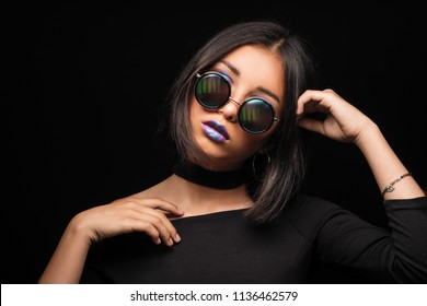 Portrait of cool crazy brunette fashionable girl in sunglasses, casual hairdo on black background. Woman like bitch with pretty makeup big lips