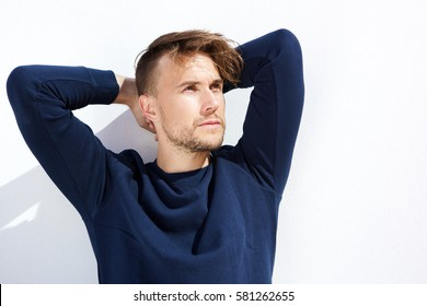 Portrait of cool fashion guy looking away with hands behind head