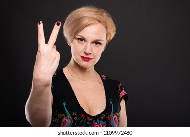 Portrait of cool fashionable woman showing number two on black background with copypsace advertising area