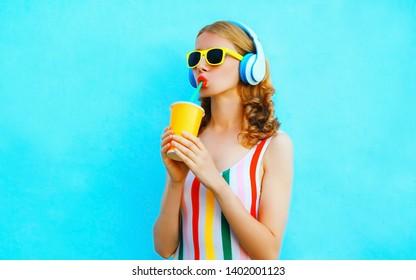 Portrait coole Mädchen trinken Fruchtsaft hören Musik in drahtlosen Kopfhörern auf buntem blauem Hintergrund