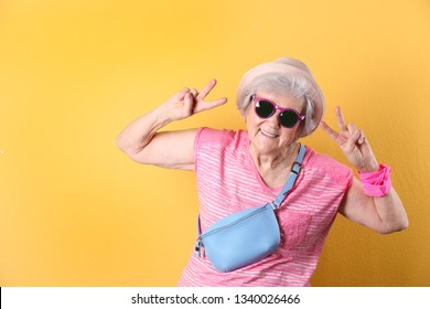 Portrait of cool grandmother on color background, space for text