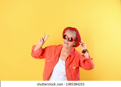 Portrait of cool grandmother on color background