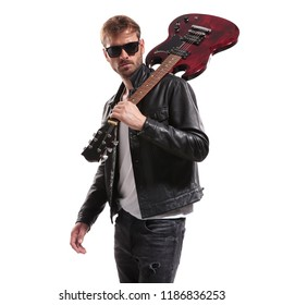 portrait of cool guitarist in black leather jacket posing with his electric guitar on shoulder while standing on white background