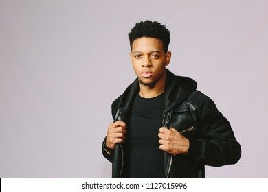 Portrait of a cool guy holding his jacket and looking at camera, isolated on grey studio background