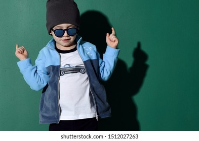 Portrait of cool kid boy in blue sunglasses, hat, fleece jacket and white t-shirt with muscle car print cool dancing looking down on green