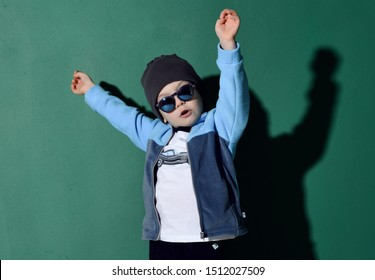 Portrait of cool kid boy in blue sunglasses, hat, fleece jacket and white t-shirt with muscle car print having fun jumping dancing with his hands up on green