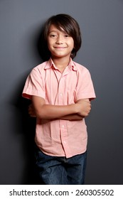 portrait of cool little boy posing with arm crossed on dark background