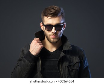 Portrait of cool looking handsome young man in casual wear standing against dark background.