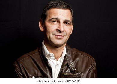 portrait of a cool mature man with leather jacket over black background