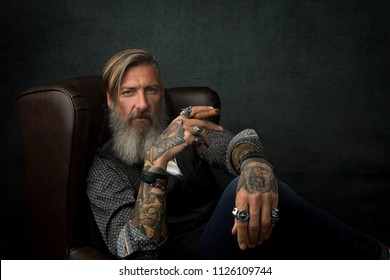 Portrait of a cool modern and bearded businessman, who is sitting in an armchair with a cigar