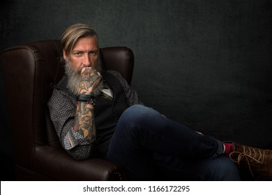 Portrait of a cool modern bearded businessman, who is sitting in an armchair