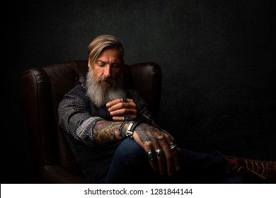 Portrait of a cool modern pensive bearded businessman, who is sitting in an armchair