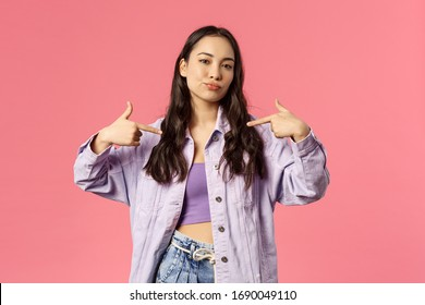 Portrait of cool and sassy stylish young woman pointing at herself with confident face, smirk and look camera as what you waiting for, pick me, bragging, being boastful, pink background
