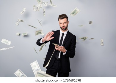 Portrait of cool stunning rich wealthy manager entrepreneur company owner waste money dollars deposit flying falling air over grey color background dressed black jacket pants blazer isolated