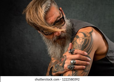 Portrait of a cool, tattooed biker with sunglasses and wind in his hair