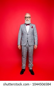 Portrait of cool, virile, harsh, perfect old man in checkered grey tuxedo and eyewear, standing, isolated on red background, looking at camera