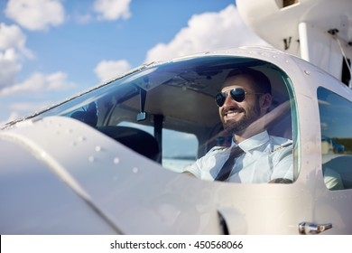 Portrait of cool young adult pilot sitting in private air plane ready to take off. Bright summer day, handsome male model