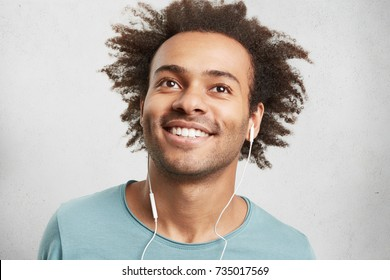 Portrait of cool young black man with curly hair, has cheerful expression, smiles broadly, demonstrates white perfect teeth, listens to jazz or pop music, looks up dreamy, enjoys good atmosphere