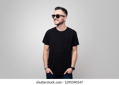 Portrait of cool  young gay in black tshirt and sunglasses. put hands in  pockets while looking away