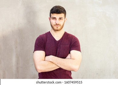 Portrait of cool young guy with beard posing with arms crossed
