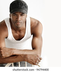Portrait of a cool young man leaning on chair in white tank and trendy cap against neutral background