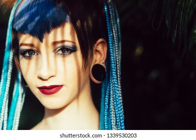 Portrait of cool young woman with blue hair braids
