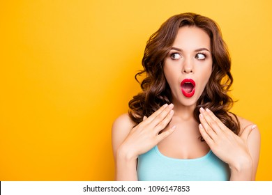 Portrait with copy space for advertisement of shocked afraid woman looking with eyes at empty place having wide open mouth eyes gesturing palms isolated on yellow background
