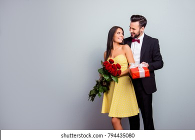 Portrait with copy space of attractive couple in formal wear, woman in dress holding bouquet of red roses, man in tux embracing her from back side and presenting a packaging red case with gift