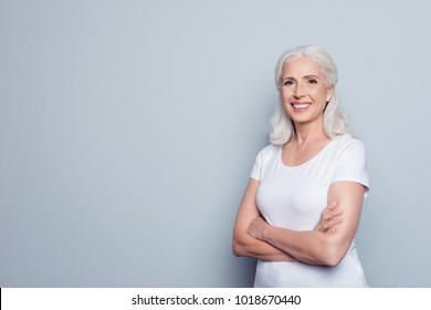 Portrait with copy space of cheerful, happy, aged, mature, nice woman standing with crossed arms over gray background