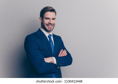Portrait with copy space of cool, stunning, brunet, smiling man with stubble in blue suit with tie, having his arms crossed, looking at camera, isolated on grey background