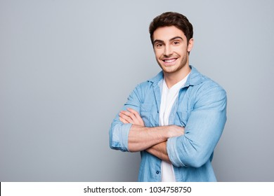 Portrait with copy space, empty place of stunning, sexy, smiling, cool man in jeans shirt having his arms crossed, looking at camera, isolated on grey background