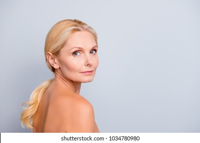 Portrait with copy space, empty place for product, advertisement, concept, charming, pretty, attractive woman with perfect skin after cream, massage, balm, mask, lotion, isolated on grey background