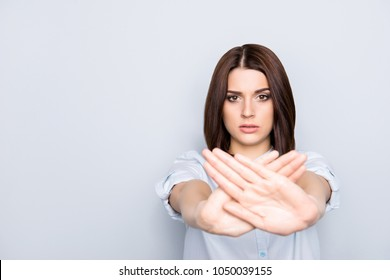 Portrait with copy space empty place of pretty, charming, stylish, nice woman making prohibition symbol with two crossed palms front to the camera, isolated on grey background
