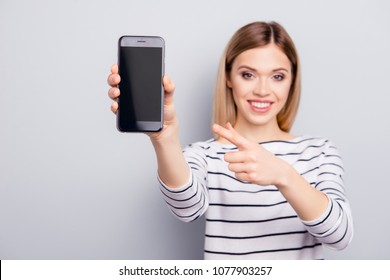 Portrait with copy space, empty place of pretty, charming, stylish, woman showing black touch screen of smart phone to the camera and pointing with forefinger on gadget, isolated on grey background