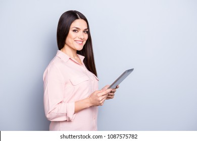 Portrait with copy space empty place of pretty charming confident trendy woman in classic shirt having tablet in hands looking at camera isolated on grey background