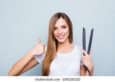 Portrait with copy space empty place of pretty, cute, charming girl having straightener in hand, showing thumb up with fingers, isolated on grey background, looking at camera, advertisement concept