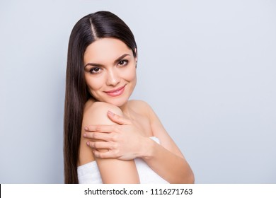 Portrait with copy space empty place for advertisement product enjoying body skin after exfoliation wrapped in white towel touching shoulder isolated on grey background. Wellness wellbeing concept