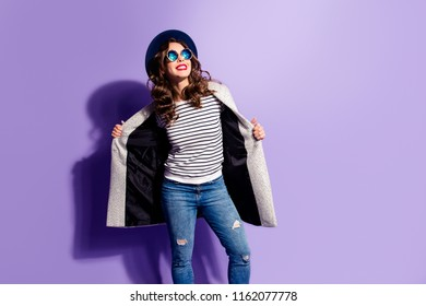 Portrait with copy space empty place of charming pretty girl in striped outfit open overcoat looking away enjoying sunshine light isolated on violet background