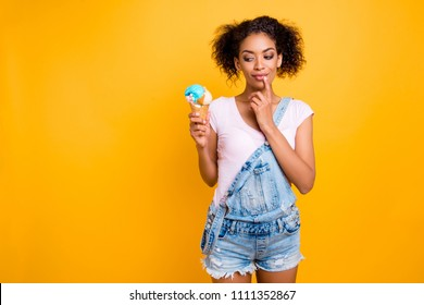 Portrait with copy space of foxy dreamy girl in jeans overall looking at ice cream in waffle cone holding finger on chin isolated on yellow background. Weight loss healthy lifestyle concept