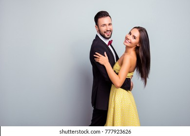 Portrait with copy space of love story of cute, cheerful, attractive, sexy couple in elegant outfit, tux, hugging, dancing, looking at camera, standing over grey background on party