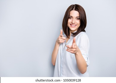 Portrait with copy space of modern, caucasian, nice, cool, perfect, charming, stylish, pretty woman with hairstyle in shirt pointing two index fingers to the camera over grey background