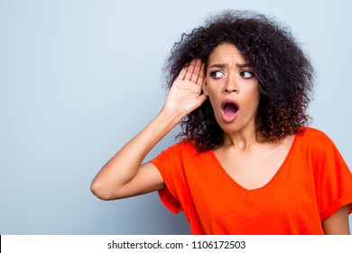 Portrait with copy space of shocked worried woman with wide open mouth holding hand near ear listening bad information gossips isolated on grey background