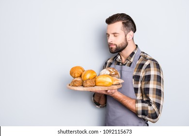 Portrait with copyspace of attractive serious man with stubble in uniform having tray with bakery products in hands, smelling scent with close eyes, isolated on grey background