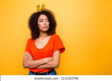 Portrait with copy-space empty place for advertisement of proud arrogant woman with modern hairdo holding arms crossed looking at empty place with offensive expression isolated on yellow background