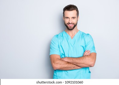 Portrait with copyspace, empty place of  joyful cheerful man with stubble in blue lab uniform, having his arms crossed, looking at camera isolated on grey background