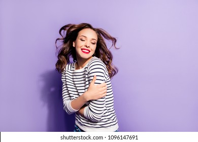 Portrait with copyspace empty place of nice sensual girl feeling cold enjoying wind blow hugging herself having flying hair keeping eyes closed isolated on violet background