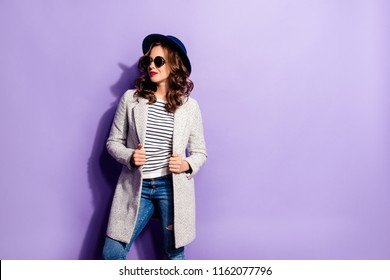 Portrait with copyspace empty place of pretty trendy girl looking away posing over violet background wearing hat glasses overcoat jeans striped clothes