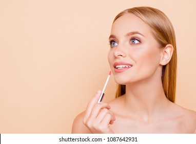 Portrait with copyspace empty place for product of cute, charming joyful girl testing new lip gloss isolated on beige background, perfection, wellbeing advertisement concept