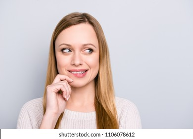 Portrait with copyspace of foxy thoughtful girl biting low lip touching chin with hand looking at empty place with eyes developing plan isolated on grey background